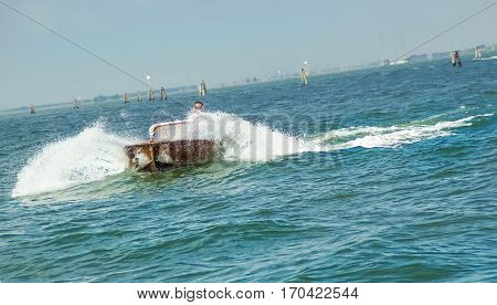 Speedboat splashing in the blue Venice lagoon