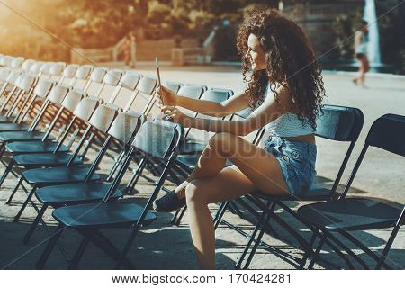 Curly brunette girl on empty seat rows of folding chairs talking with her friend by video multiple black chairs on street before event on sunny day in park with woman with touch pad sitting on them