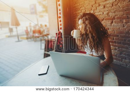 Beautiful curly brunette girl drinks tea or coffee while sitting with portable laptop in street cafe charming dreamy woman using her computer during rest in cafe with cup of tea