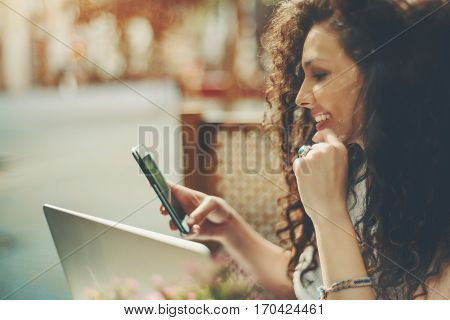 Smiling beautiful white caucasian girl with black curly hair sitting in street cafe and texting message on her phone happy freelancer woman browsing site on her smartphone with opened laptop in cafe