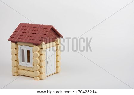 Toy House On A White Background, Near A Place Under An Inscription