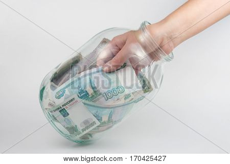 Hand Takes Out A Three-liter Glass Jars Thousand Russian Rubles