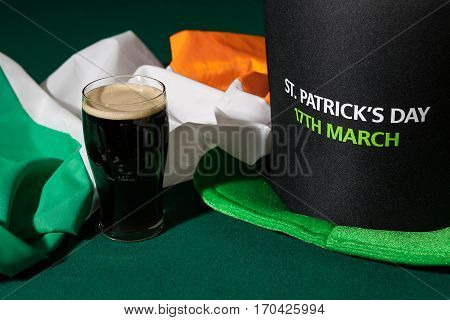 St Patrick day with a pint of black beer hat and irish flag over a green table