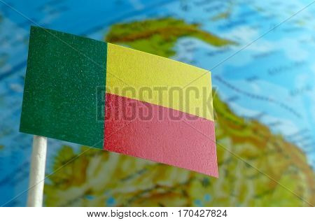 Benin Flag With A Globe Map As A Background Macro