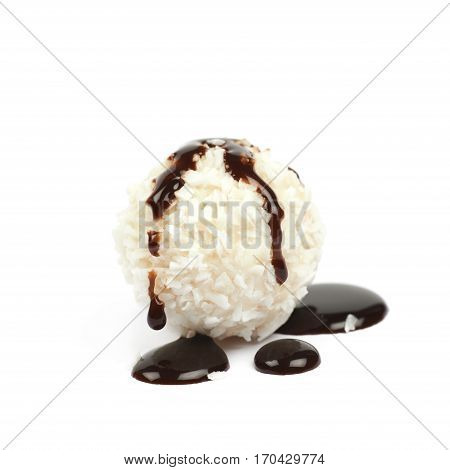 White chocolate ball candy covered with the coconut flakes ad spilled with the hot chocolate syrup, composition isolated over the white background