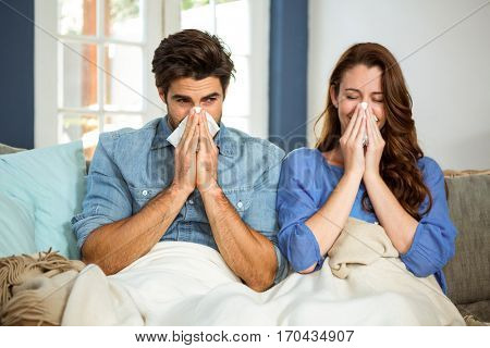 Young couple blowing their nose in tissue at home