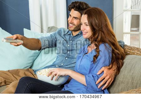 Young couple having popcorn while watching television in living room