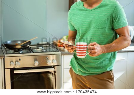 Mid section of man using mobile phone and holding a coffee cup in kitchen at home
