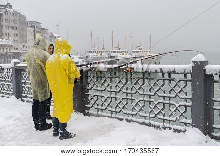 ISTANBUL, TURKEY, JANUARY 8,2017: People trying to catch fish under heavy snow on top of Galata Bridge, Istanbul, Turkey.