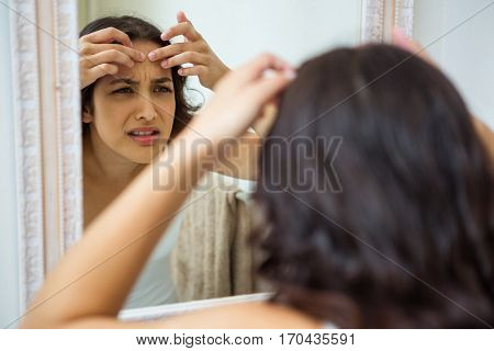 Woman popping her pimple in bathroom