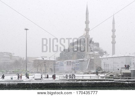 ISTANBUL, TURKEY, JANUARY 8, 2017: People trying to walk under heavy snow at the coastline of Eminonu, New Mosque can be seen at the background.
