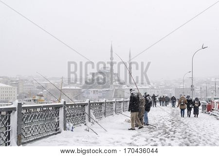 ISTANBUL, TURKEY, JANUARY 8,2017: People trying to catch fish under heavy snow on top of Galata Bridge, New Mosque at Eminonu District can be seen at the background.