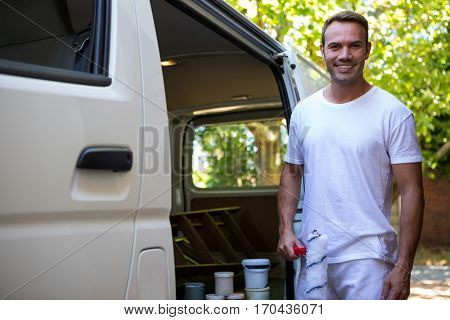 Portrait of painter holding paint roller standing near his van