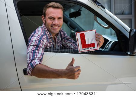 Portrait of young man gesturing thumbs up holding a learner driver sign