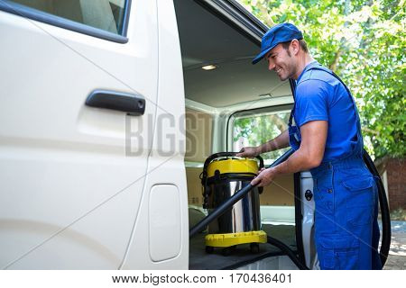 Happy janitor cleaning the car with vacuum cleaner