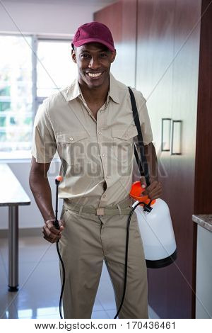 Portrait of smiling pest control man in kitchen
