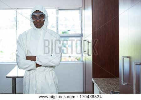 Pest control man standing in kitchen with arms crossed