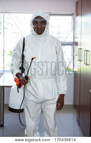 Portrait of pest control man standing with insecticide sprayer in kitchen
