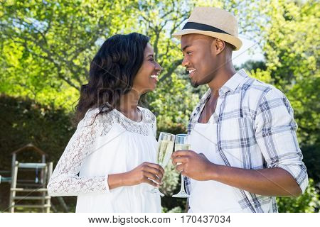 Young couple toasting glasses of champagne in the park