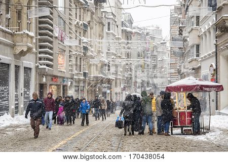 ISTANBUL, TURKEY, JANUARY 8, 2017: People walking under heavy snow at Beyoglu avenue, one of the most famous avenues in Istanbul, Turkey, visited by nearly 3 million people in a single day.