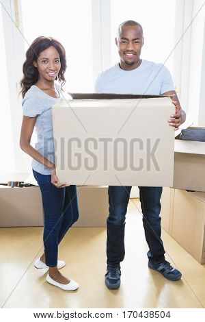 Portrait of young couple holding carton boxes in their new house