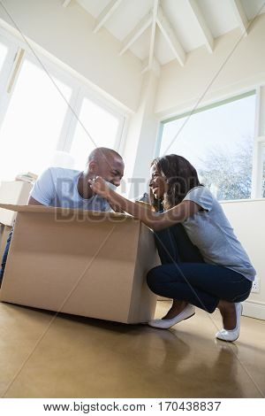 Young couple having fun while unpacking box in their new house