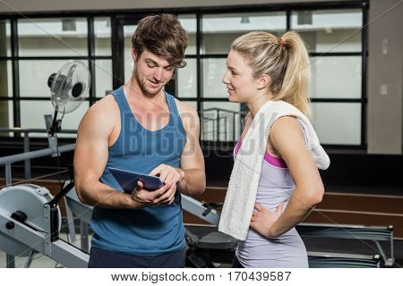 Trainer using a digital tablet while talking to a woman at gym