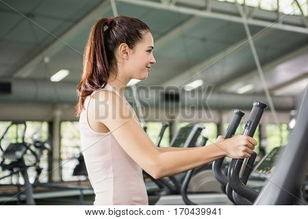 Beautiful woman exercising on the elliptical machine at gym