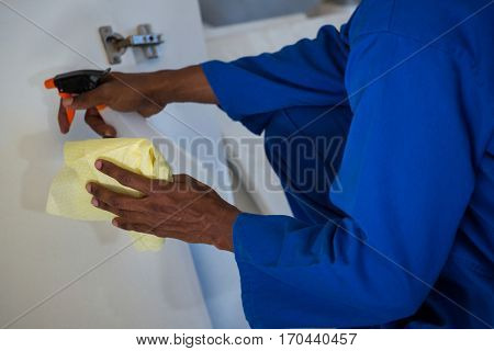 Man spraying on wooden board in a new house
