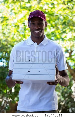 Portrait of happy delivery man holding pizza boxes