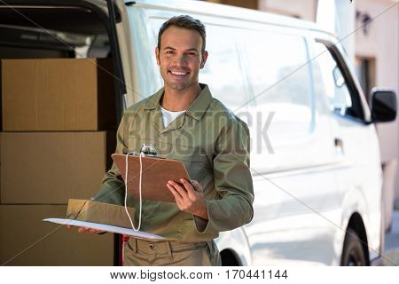 Happy delivery man holding cardboard box and clipboard next to a delivery van