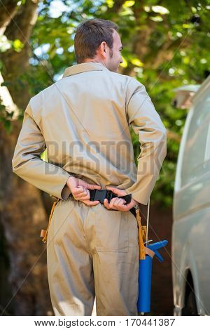 Rear view of handyman with tool belt around waist standing next to delivery van
