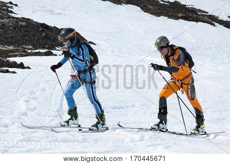 AVACHA VOLCANO KAMCHATKA PENINSULA RUSSIA - APRIL 21 2012: Open Cup of Russia on Ski-Mountaineering on Kamchatka - two ski mountaineers climb on mountain on skis strapped to climbing skins.