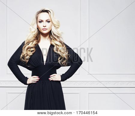 Alluring and sexy model in black dress posing over white wall. Fashion, beauty concept.