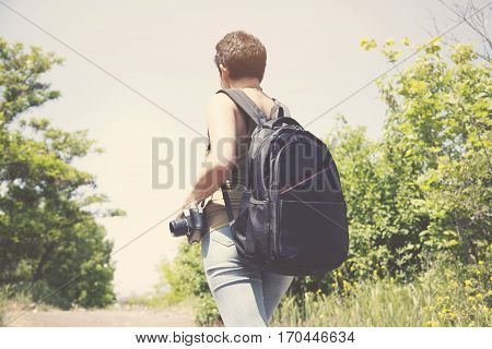 young woman with backpack and camera in nature