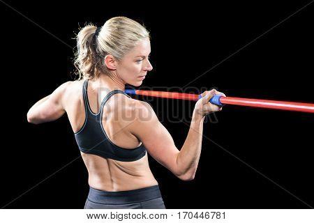 Athlete preparing to throw javelin on black background