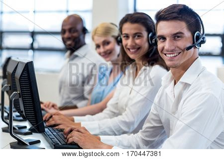 Portrait of colleagues sitting at their desk with headset in the office
