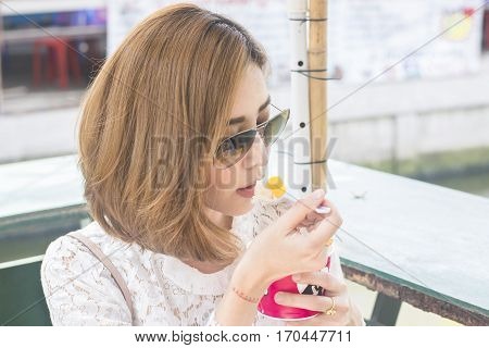 yong women aisa wear glasses eating icecream