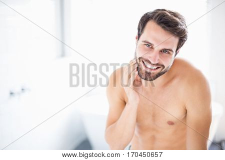 Young man checking his stubble in bathroom