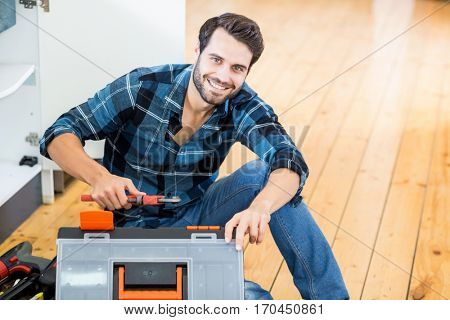 Portrait of man unpacking his tool box at home