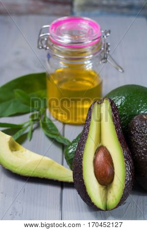 Green ripe fresh avocado with leaves whole and sliced and avocado oil