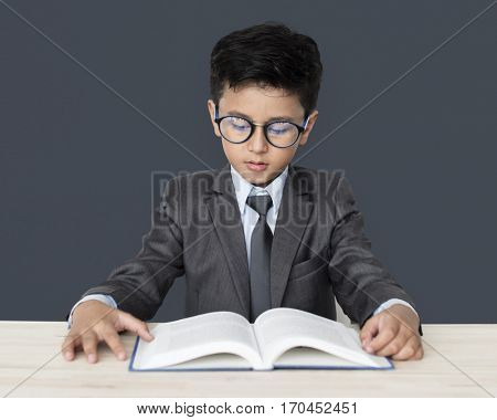 A Caucasian Boy With Glasses Reading Book Background Studio Portrait