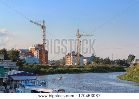 building a new house on the waterfront of the Vologda River with construction crane