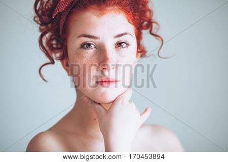 Beautiful young redhead woman with hand in her chin