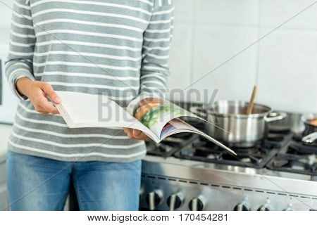 Midsection of woman reading book by stove in kitchen at home