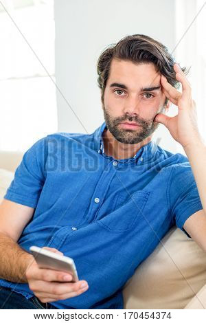 Portrait of tensed man using mobile phone while sitting on sofa at home