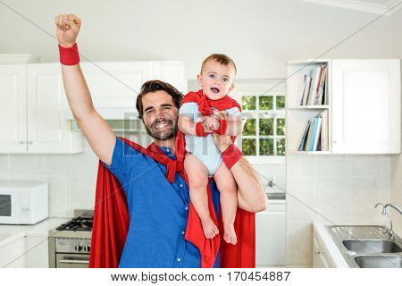 Happy father in superhero costume lifting son in kitchen