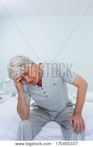 Senior man suffering from headache while sitting on bed at home
