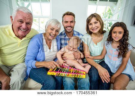 Portrait of happy multi-generation family sitting on sofa at home