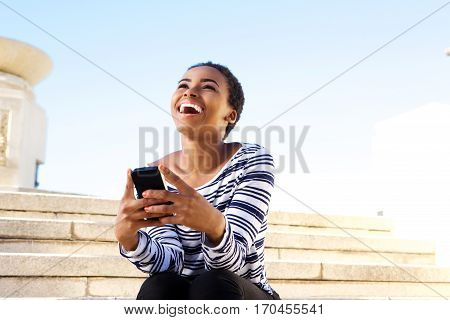 Happy Young Woman Sitting Outside Using Mobile Phone